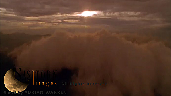 Forward tracking aerial shot, camera passes over backlit clouds towards weak sunset through higher cloud