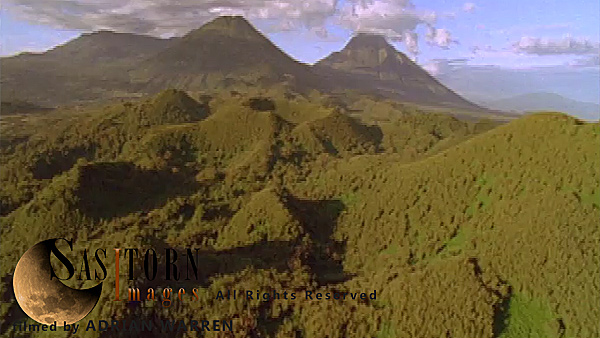 Forward tracking aerial shot, Virunga volcanoes, camera passes low over cratered forest between Sabyinyo and Visoke (Bisoke) in morning sun, Visoke (Bisoke) and cloud topped Mikeno and Karisimbi in background, camera tilts down and turns into sunlight in front of Visoke (Bisoke)