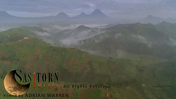 Forward tracking aerial shot, Rwandan countryside, camera passes low over farm land and mist filled valleys with exposed ridges in morning sunlight, volcanoes in background (Mt Sabyinyo, Gahinga and Muhavura)
