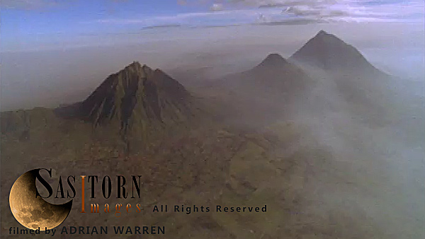 Forward tracking aerial shot, Virunga volcanoes, camera approaches distant  Mt Sabyinyo with mist shrouded peaks of Gahinga and Muhavura in distant right of shot, patchwork field visible at base of Sabyinyo
