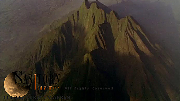 Forward tracking aerial shot, Virunga volcanoes, camera approaches Mt Sabyinyo in morning sunlight with Karisimbi, Visoke (Bisoke) and Mikeno in background, camera slowly tilts down to show detail of summit