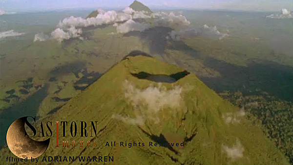 Forward tracking aerial shot, Virunga volcanoes, camera passing high over Mt Visoke (Bisoke) with Mts Sabyinyo and Gahinga in background, camera tilts down over crater lake (in shadow) camera tilts back up to show distant volcanoes surrounded by low cloud