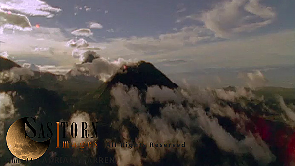 Forward tracking aerial shot of Virunga volcanoes with high and low clouds in late afternoon sun. Camera approaches Mt Visoke (Bisoke)